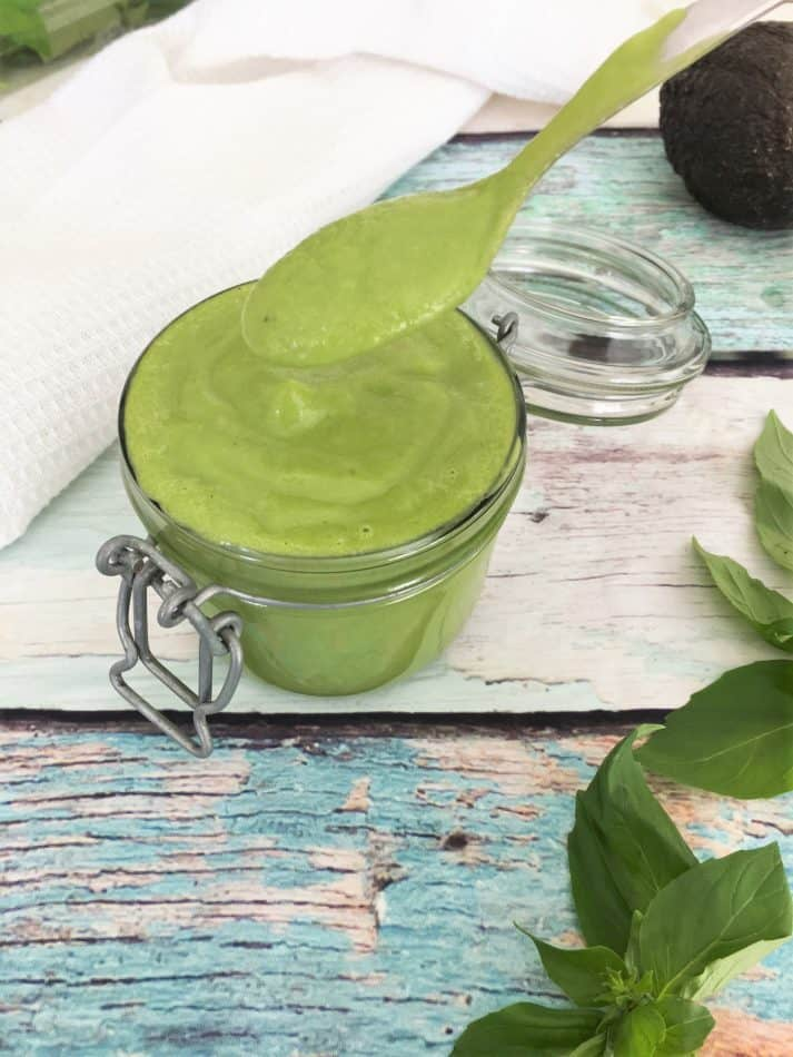 green salad dressing in jar with spoon