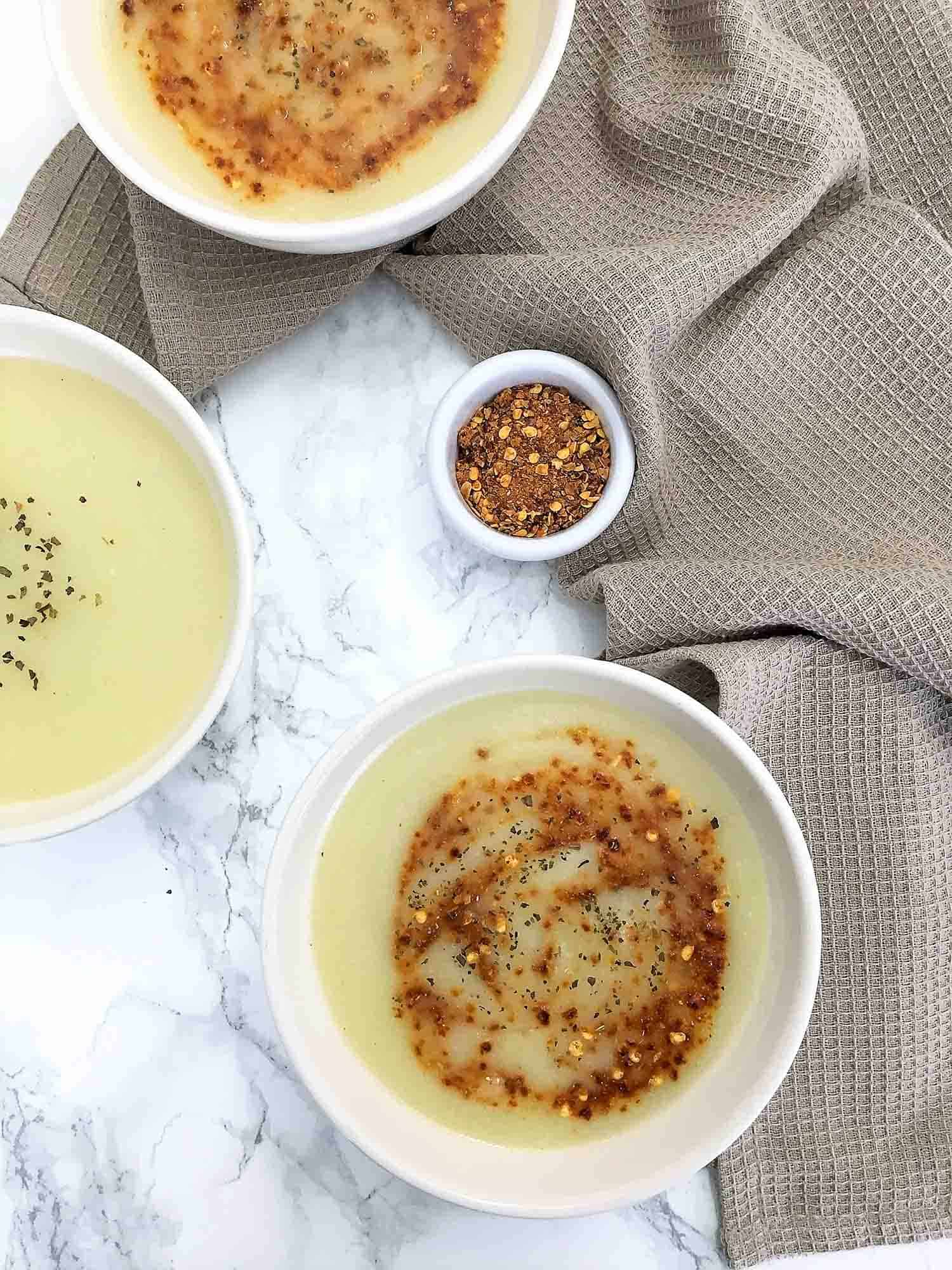 three bowls of creamy soup with brown towel beside them