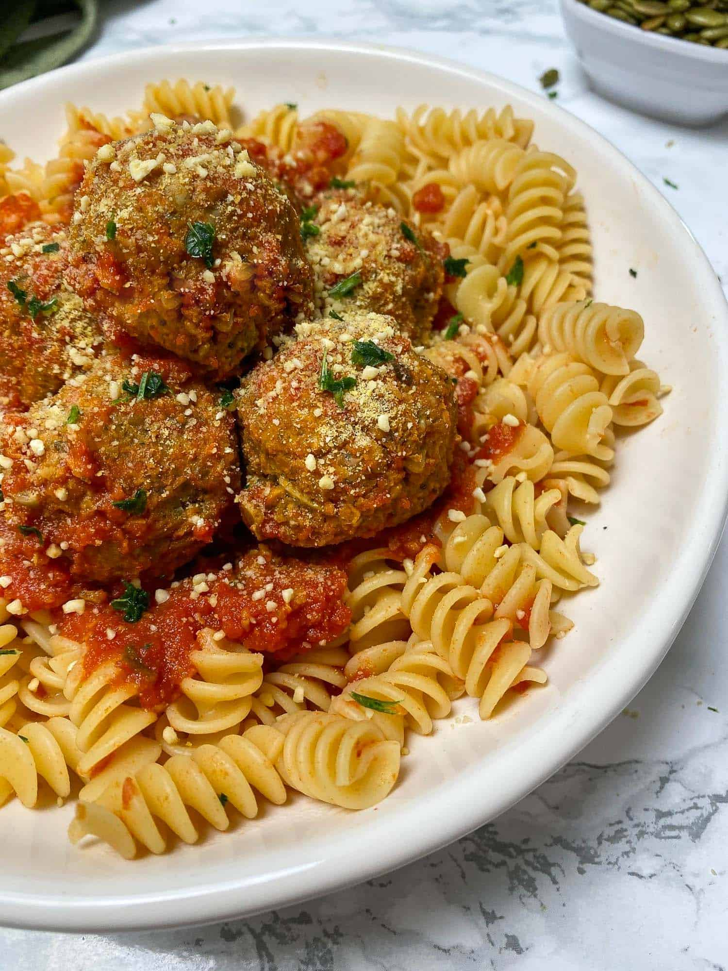 lentil meatballs over bed of rotini pasta with tomato sauce
