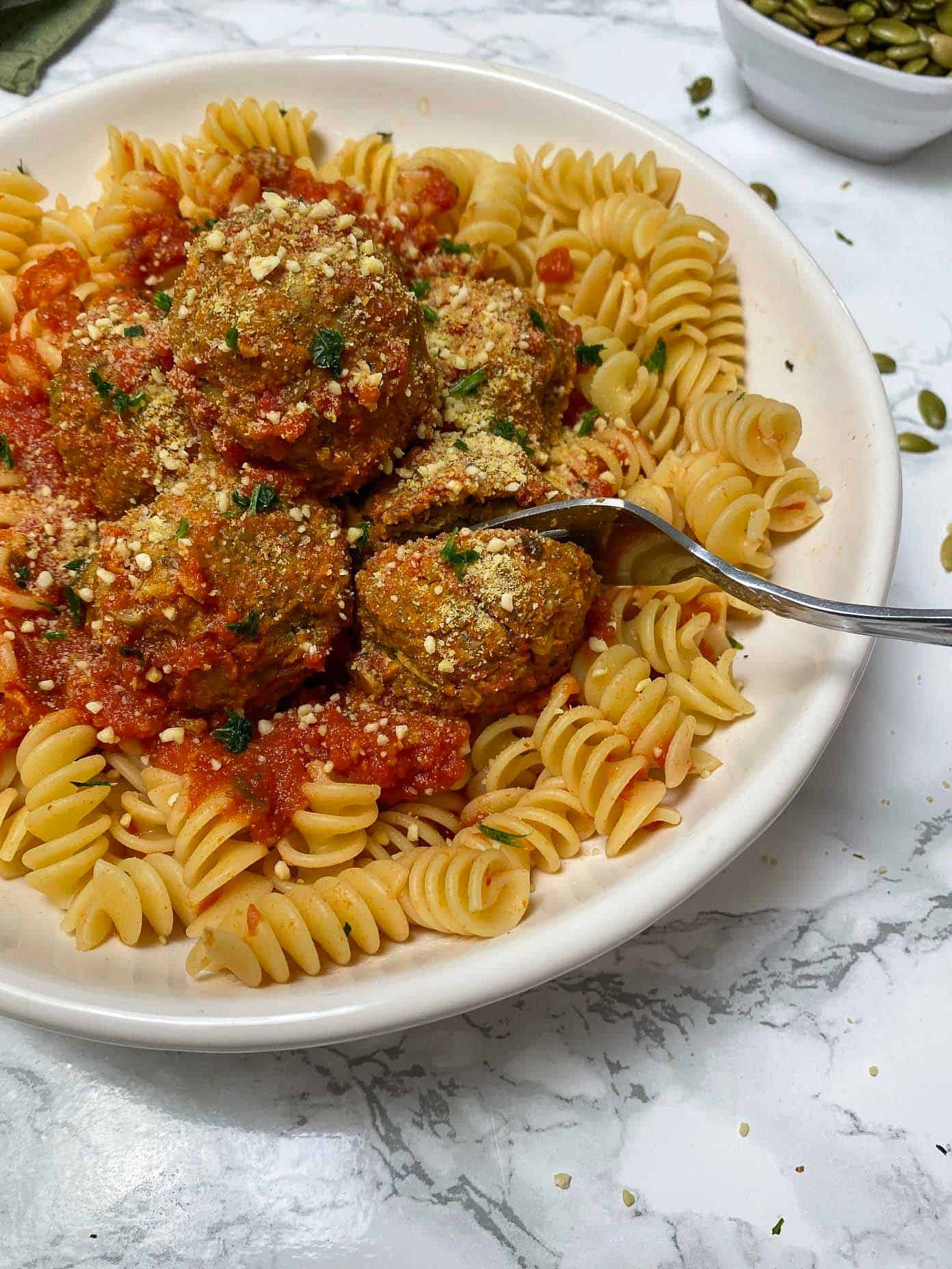 fork cutting into vegan meatball over bed of pasta