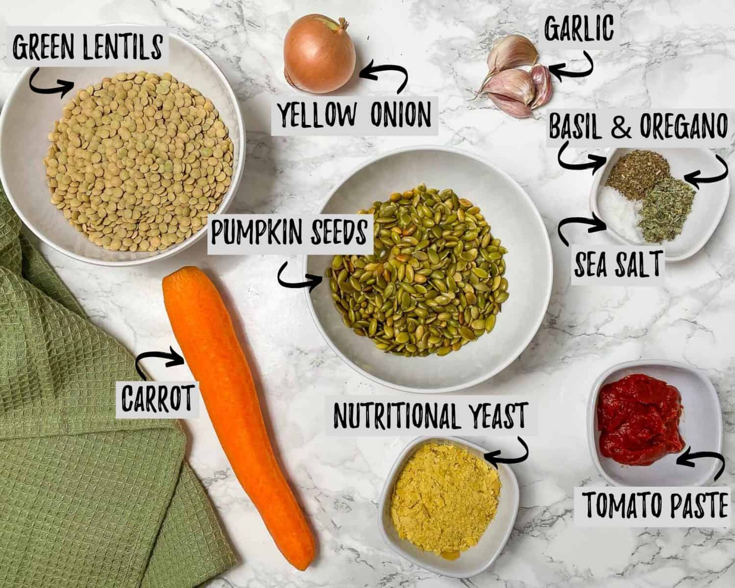 bowl of lentils, pumpkin seeds, nutritional yeast, seasoning, tomato paste, onion, garlic and carrot on marble counter