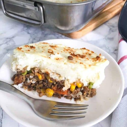slice of lentil shepherd's pie in plate with fork