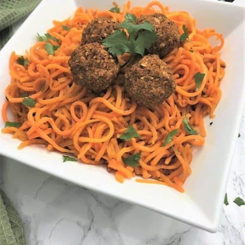 Sweet Potato Noodles topped with lentil vegan meatballs garnished with fresh cilantro