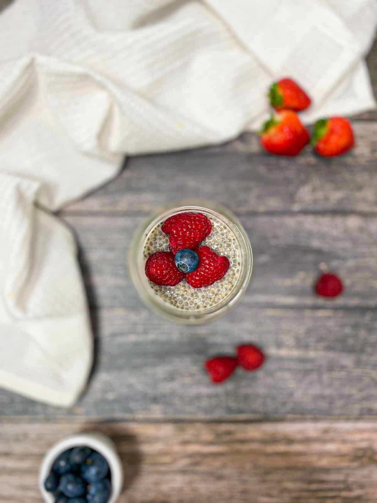 overhead view of glass jar with chia pudding inside and berries on top