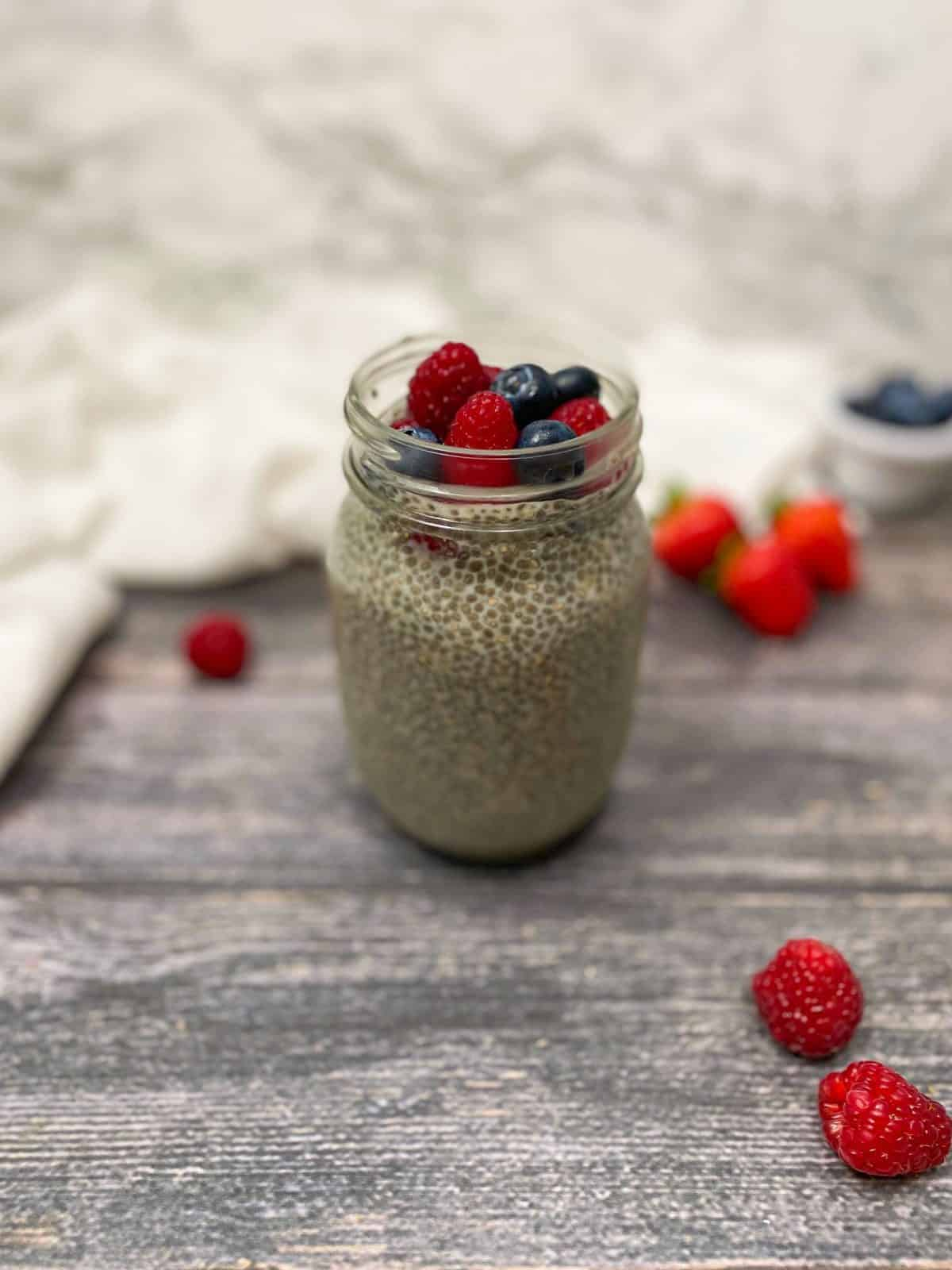 chia pudding in glass mason jar with fresh berries on top