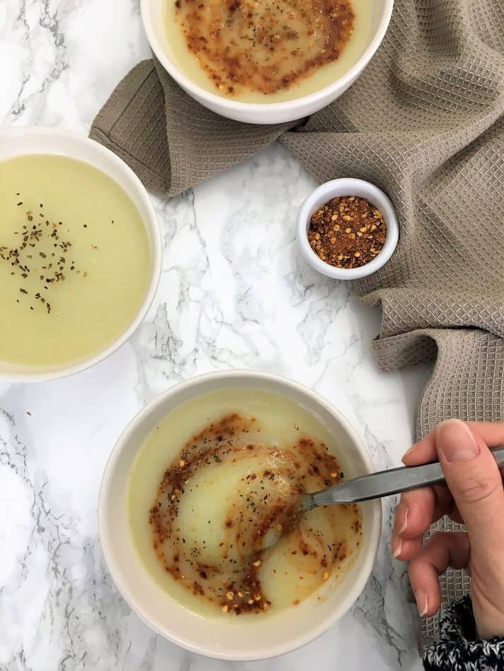 cauliflower soup in bowl with hand holding spoon