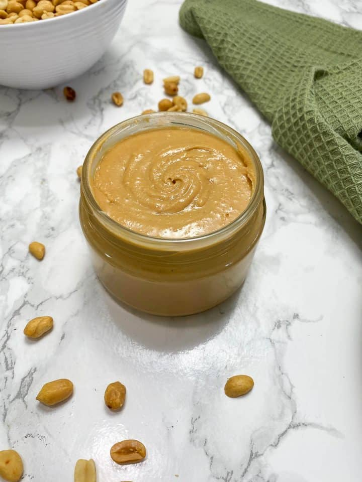 peanut butter in jar with peanuts and green towel around it