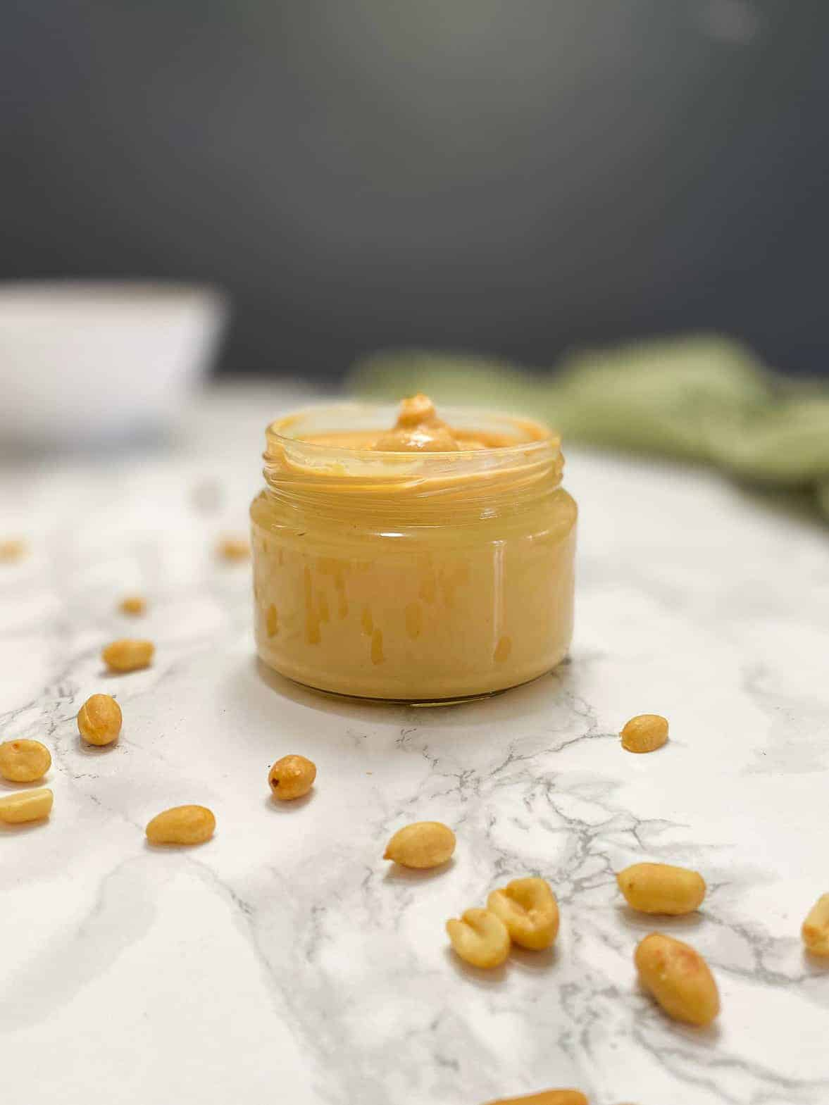 peanut butter in glass jar with peanuts scattered around the jar