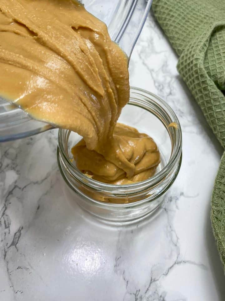 pouring peanut butter from blender into jar