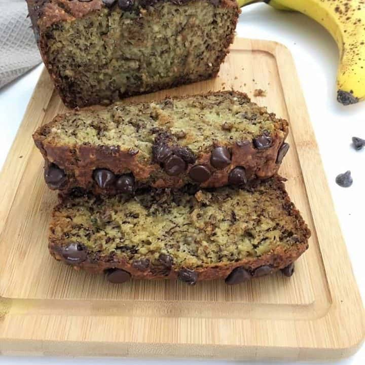 banana bread loaf on cutting board with two slices