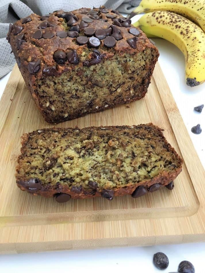 one slice of banana bread with loaf in background