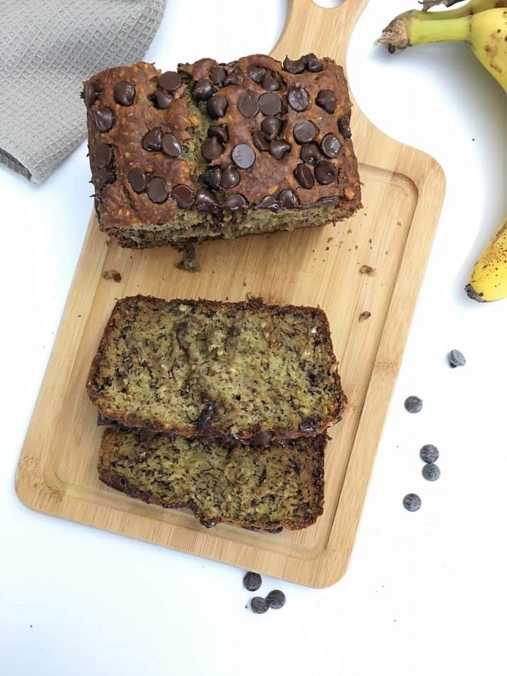 chocolate chip banana bread on cutting board with chocolate chips fallen