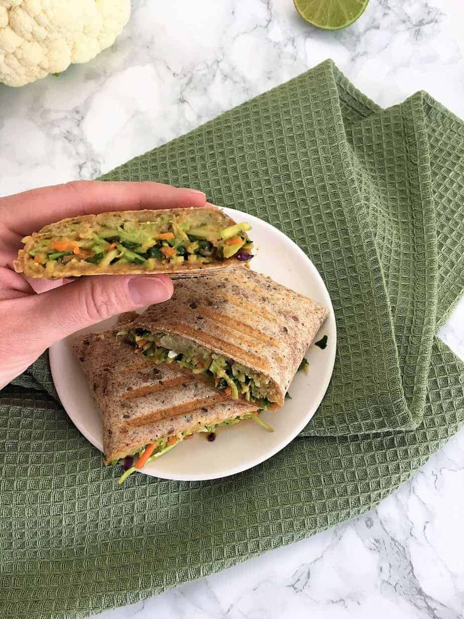 hand holding asian slaw veggie wrap over green towel