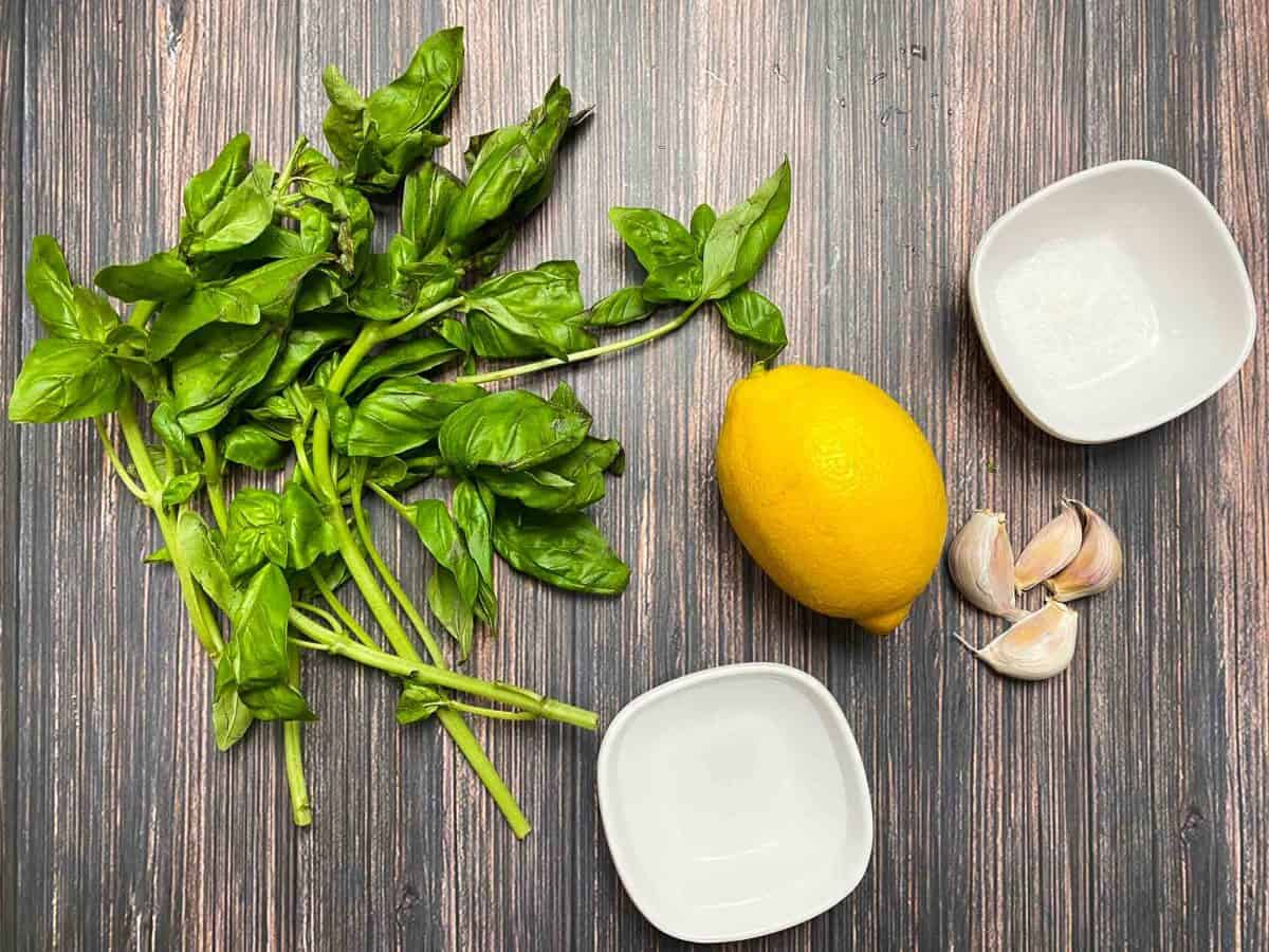 basil leaves, lemon, garlic cloves and cup of water on brown deck