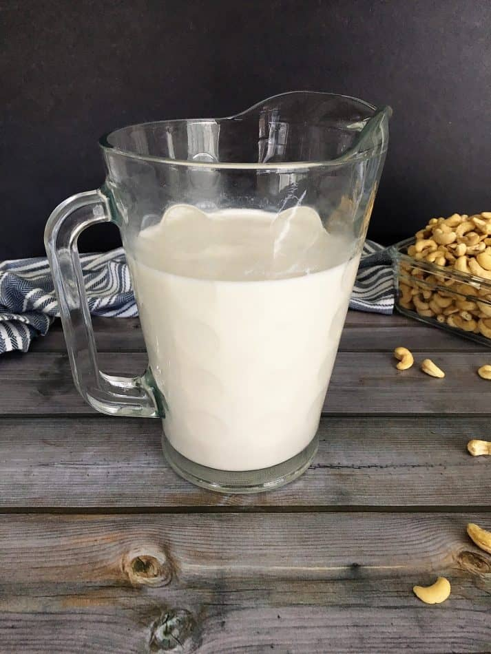 glass pitcher filled with cashew milk
