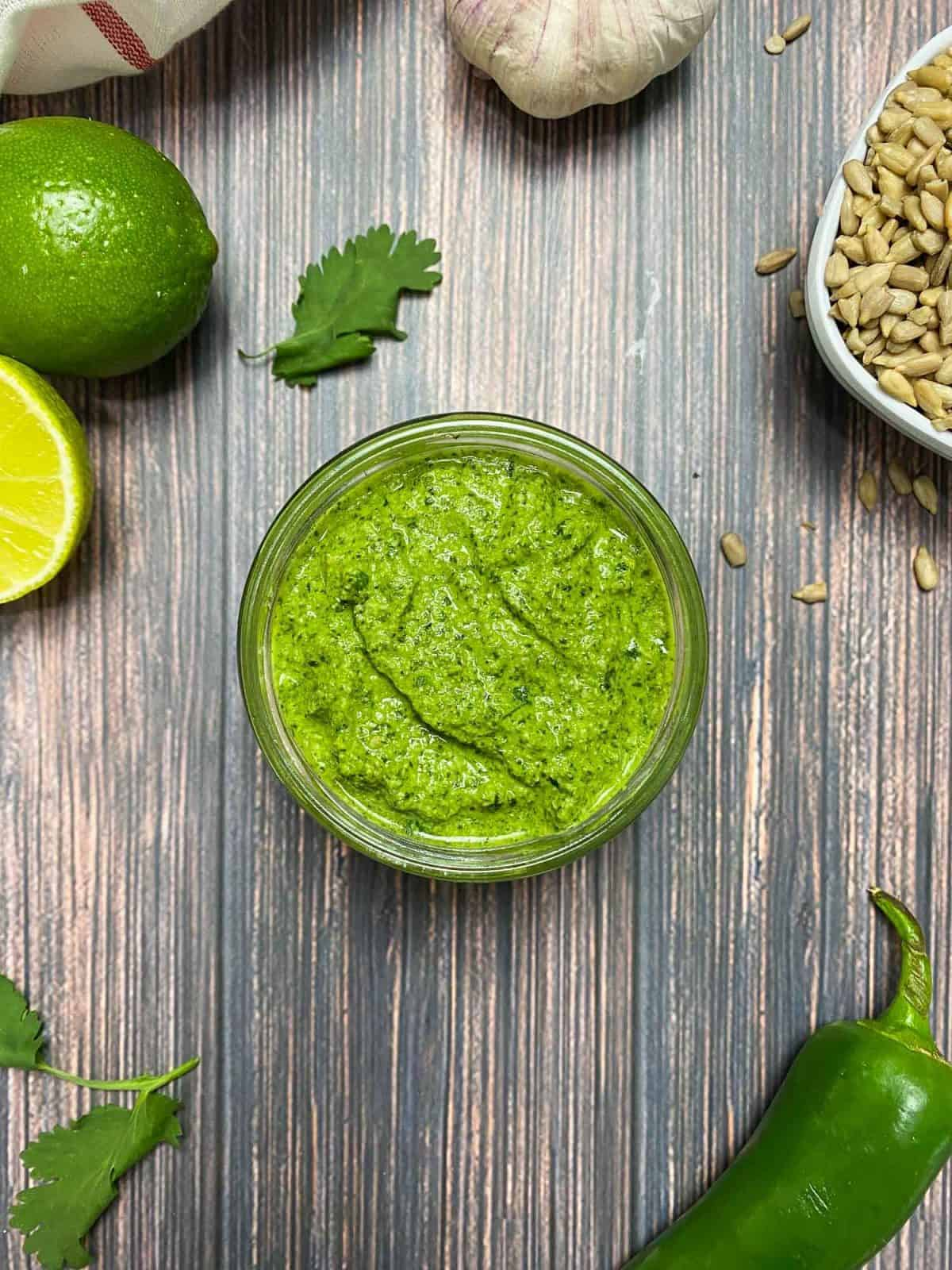 open jar of pesto sauce with lime and cilantro in background