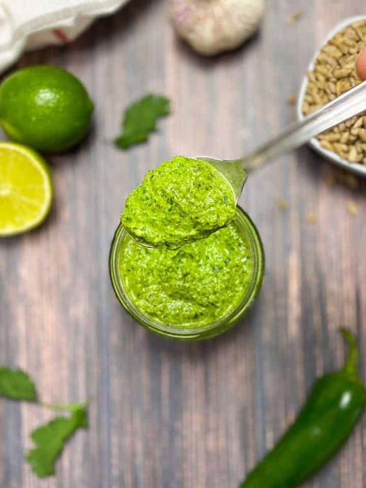cilantro pesto in glass jar with lime, sunflower seeds and jalapeno in the background