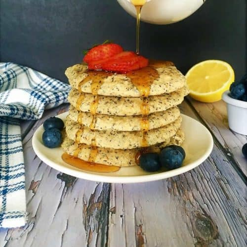 stack of pancakes with maple syrup being poured on top