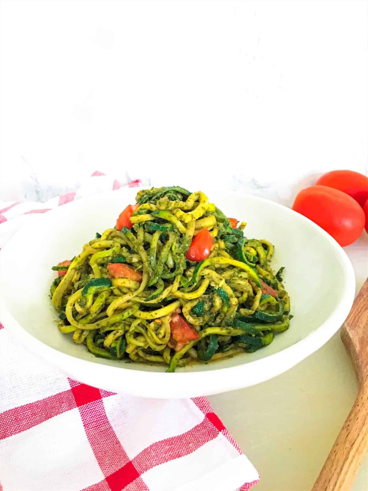 pesto zucchini noodles in plate with tomatoes in background