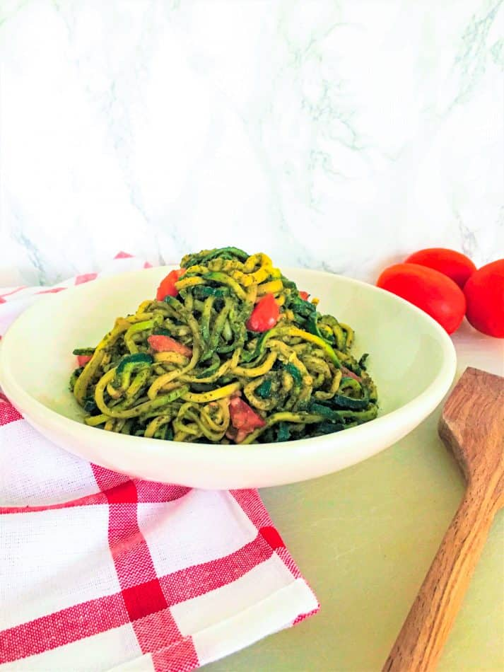 pesto zoodles in bowl with diced tomatoes
