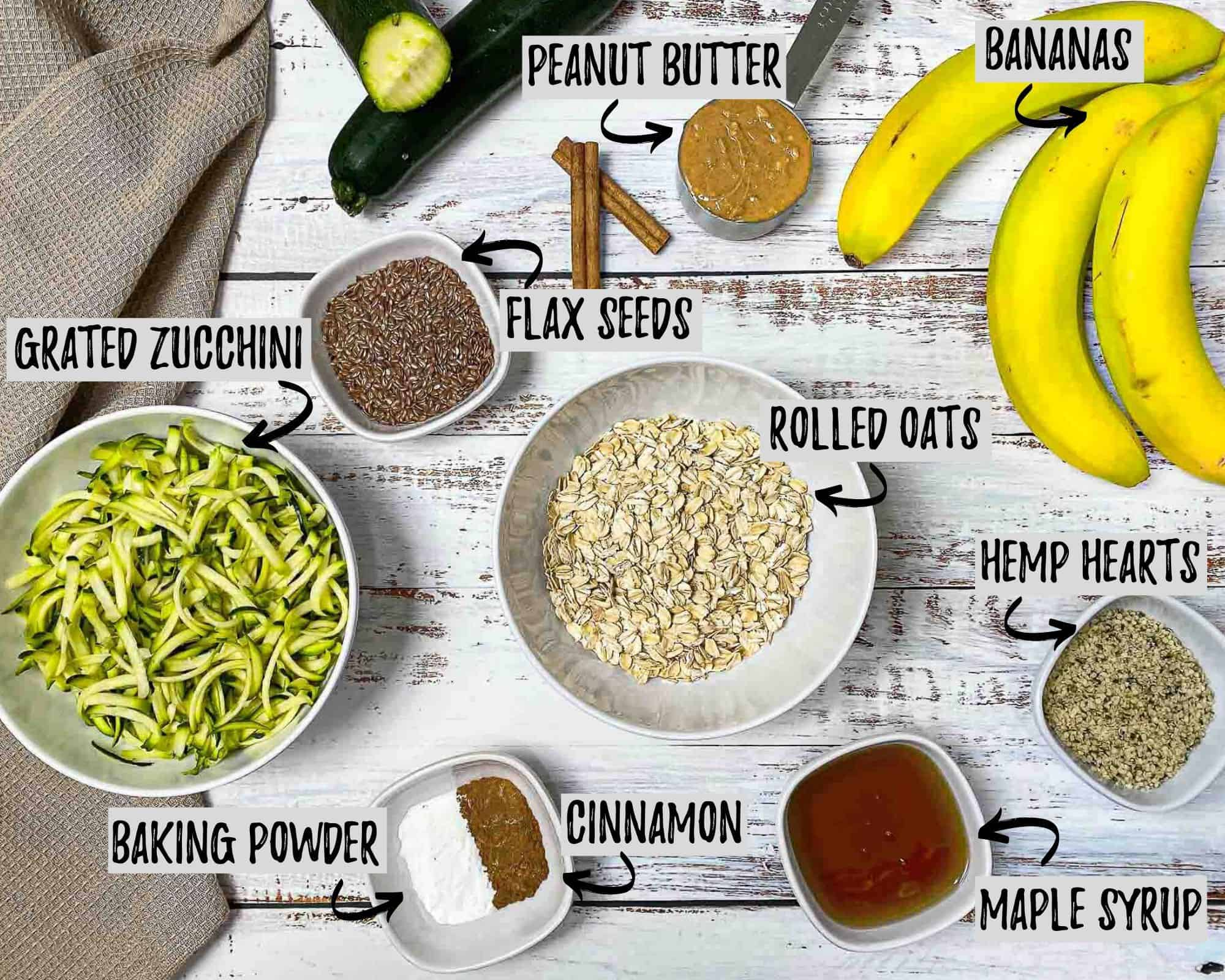 bowl of oats, grated zucchini, maple syrup, cinnamon, baking powder, peanut butter, flax seeds, and bananas