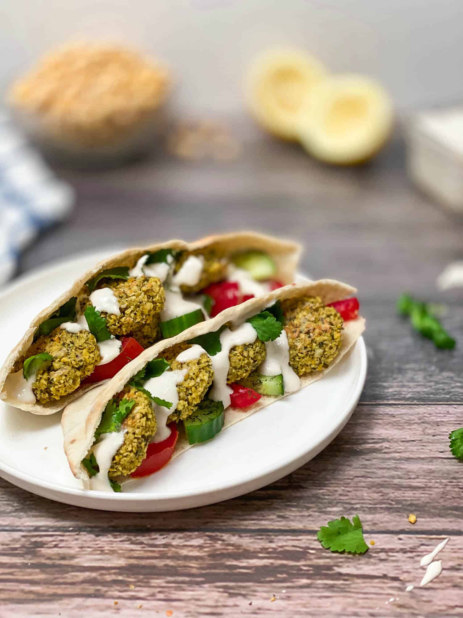two open pitas on white plate with falafel and tahini