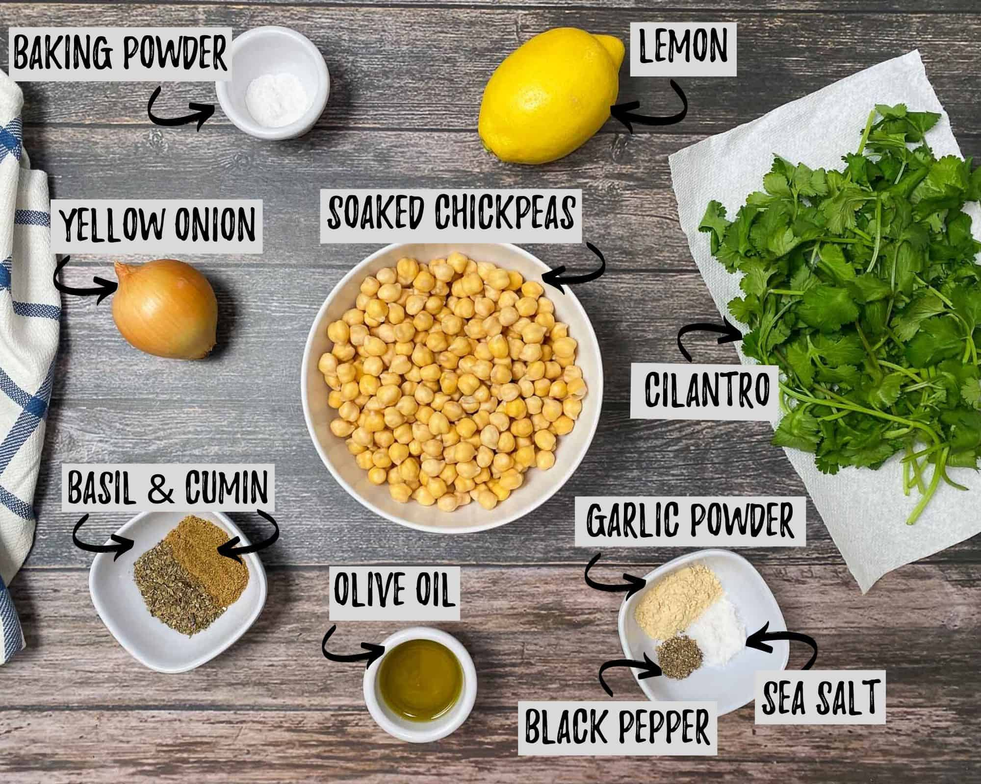bowl of chickpeas, seasoning, olive oil, baking powder, lemon, onion, and cilantro on grey deck