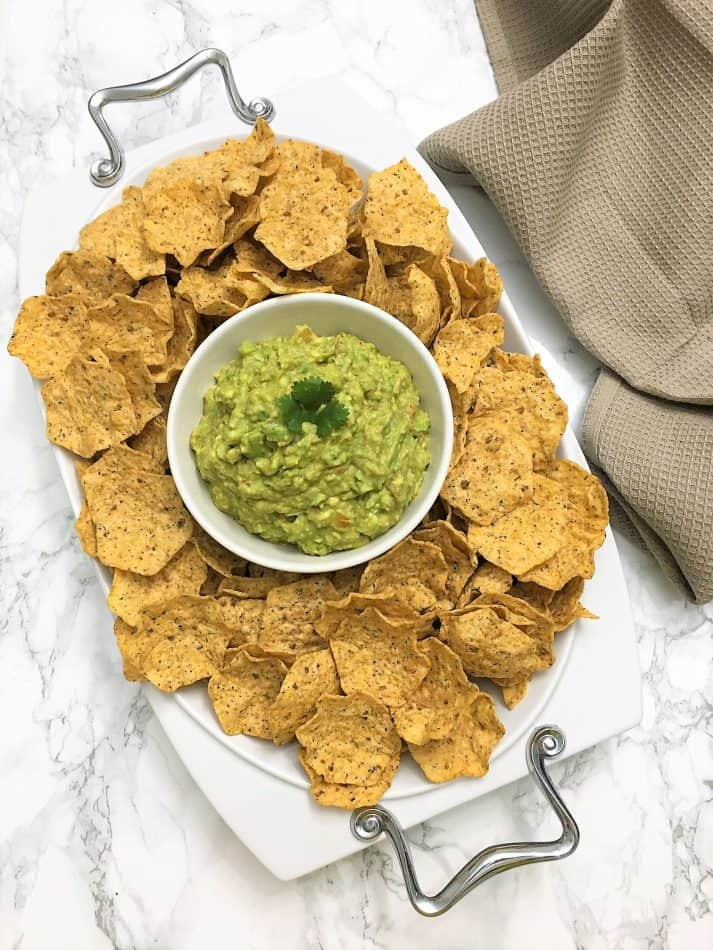 guacamole in the middle of a platter of tortilla chips