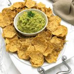 Guacamole in bowl with tortilla chips surrounding it in a platter
