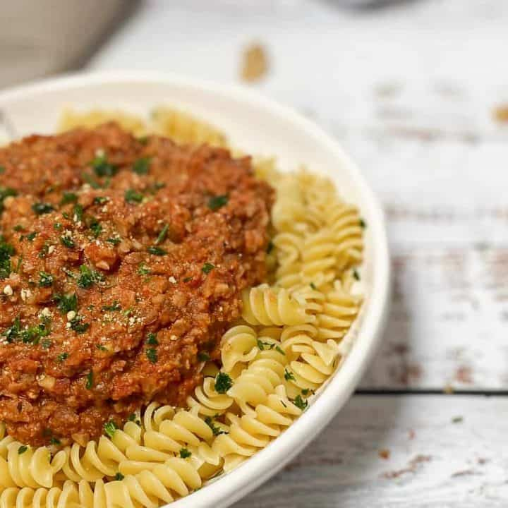 side view of white dish filled with fusili pasta and covered in bolognese sauce