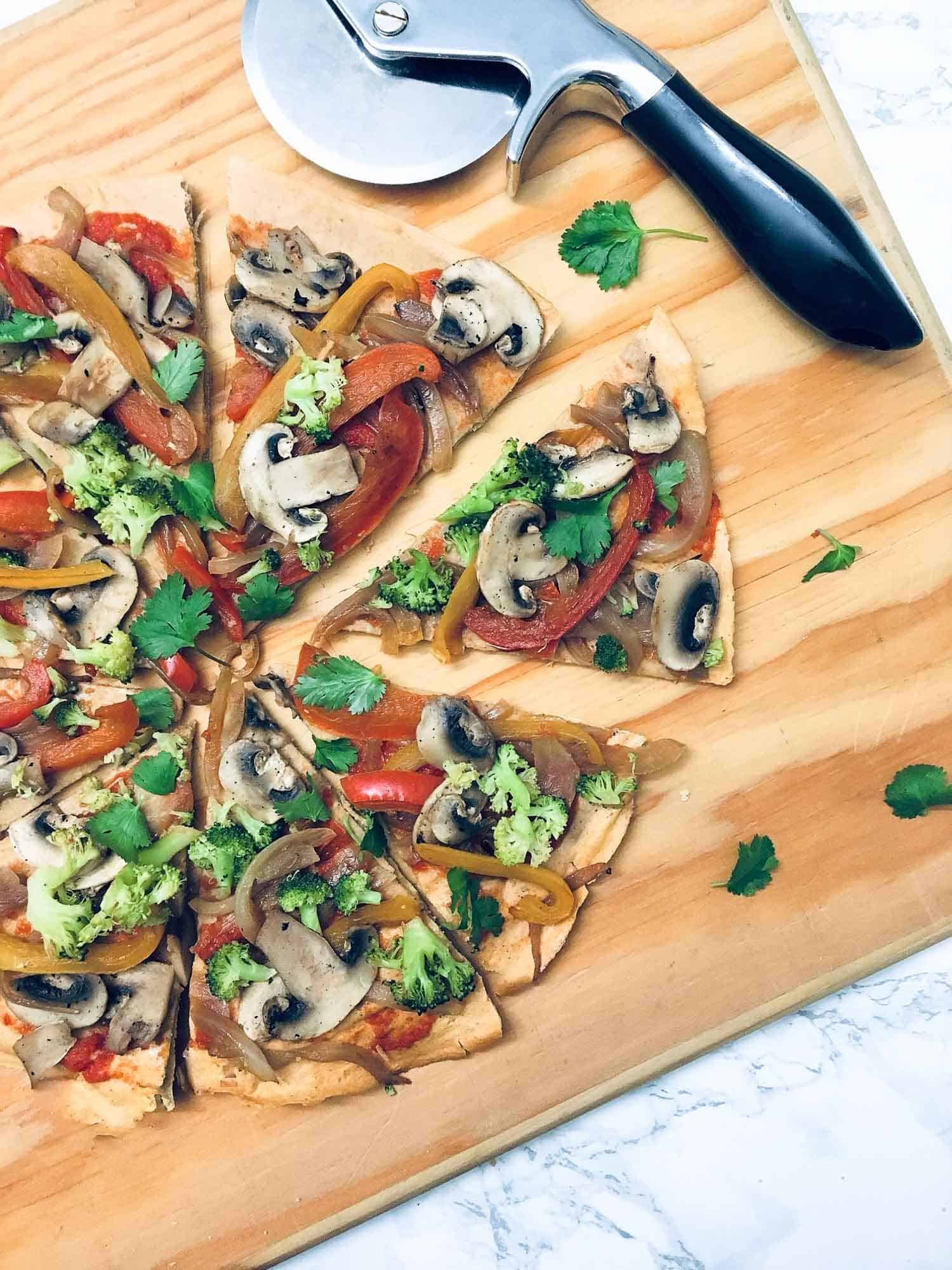 triangular slice of pizza pulled away from entire pizza on wooden cutting board