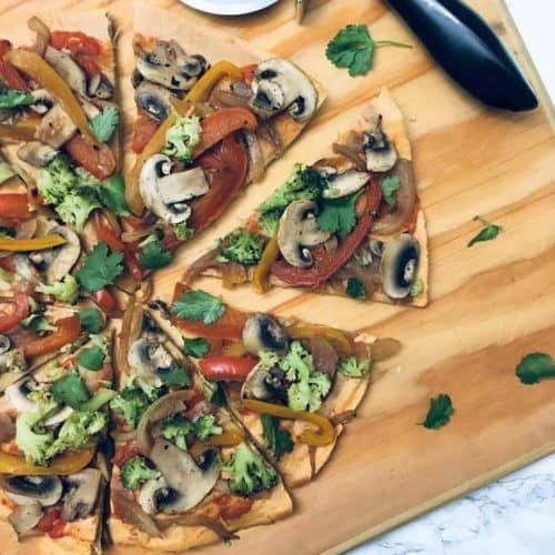 Lentil Pizza Crust topped with veggies on a cutting board