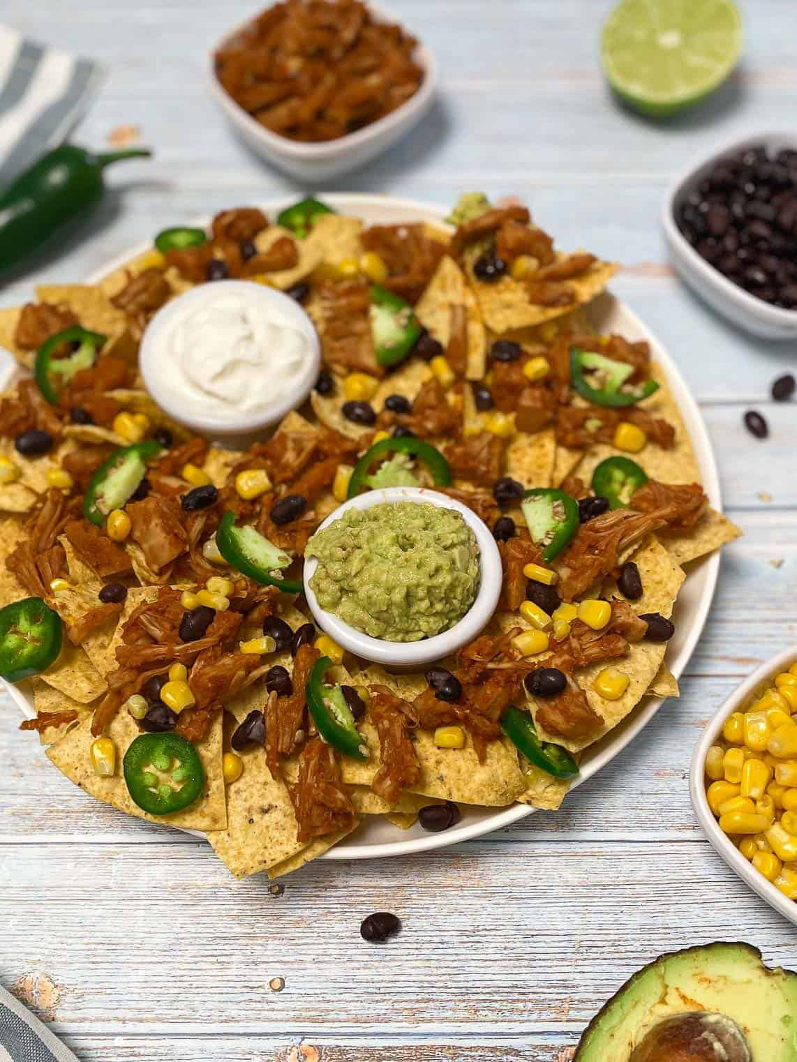 platter of tortilla chips with jackfruit, jalapeno and corn on top