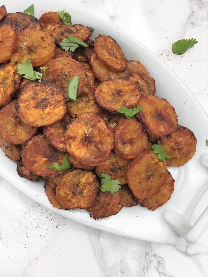 baked plantain chips on serving dish garnished with cilantro