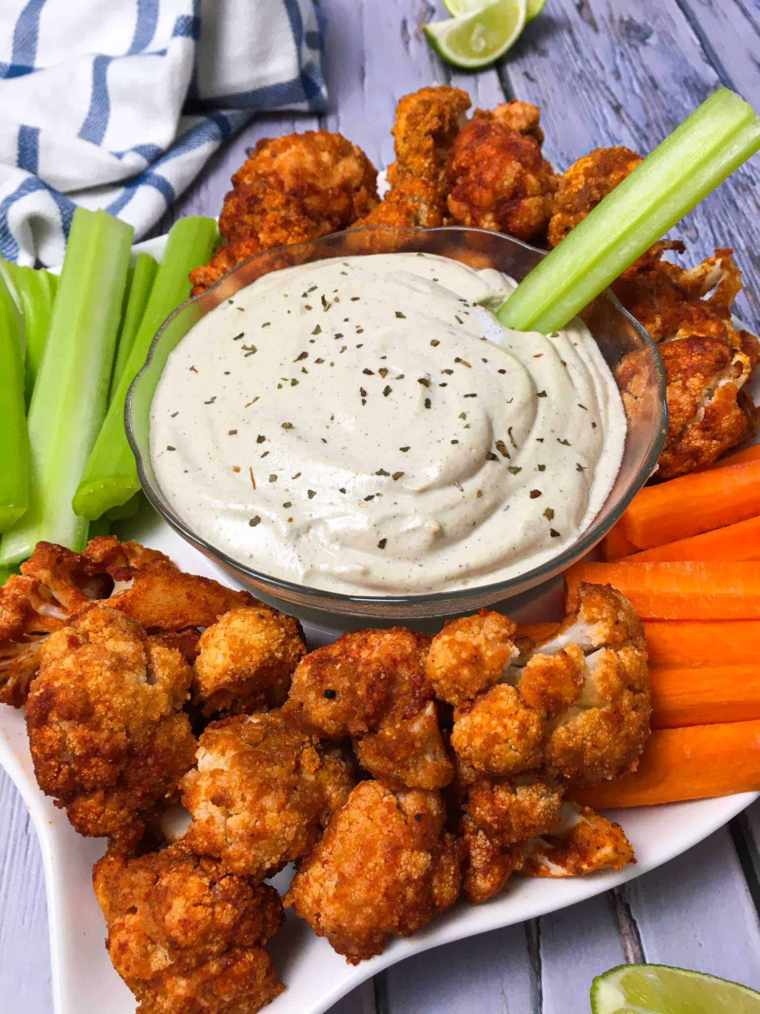 celery stick in bowl of ranch dressing surrounded by cauliflower buffalo wings