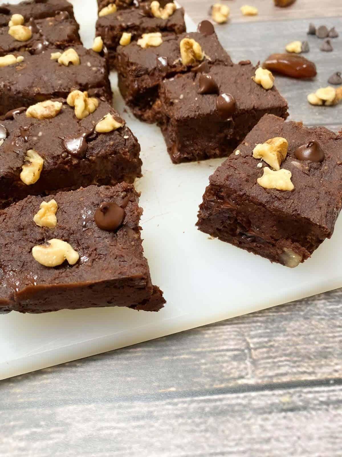 vegan brownies on cutting board with walnuts on top