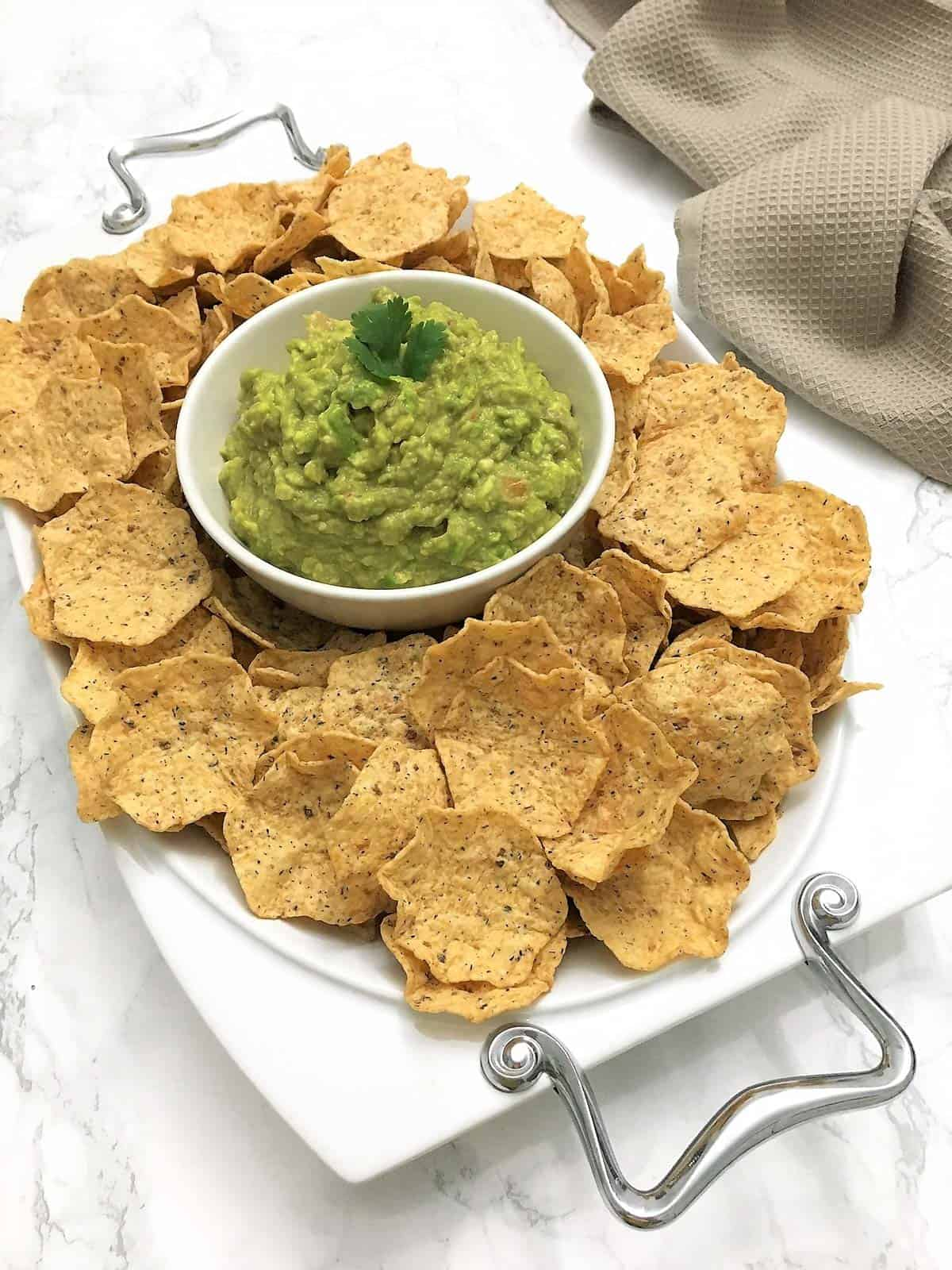 bowl of guacamole in platter with chips around it