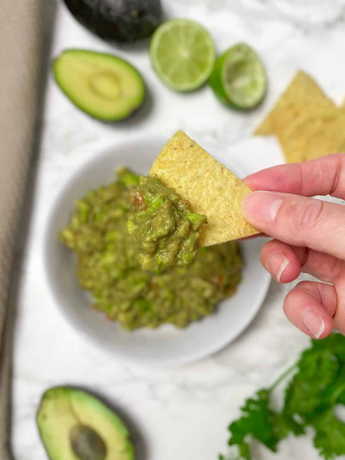 chip dipping into bowl of guacamole