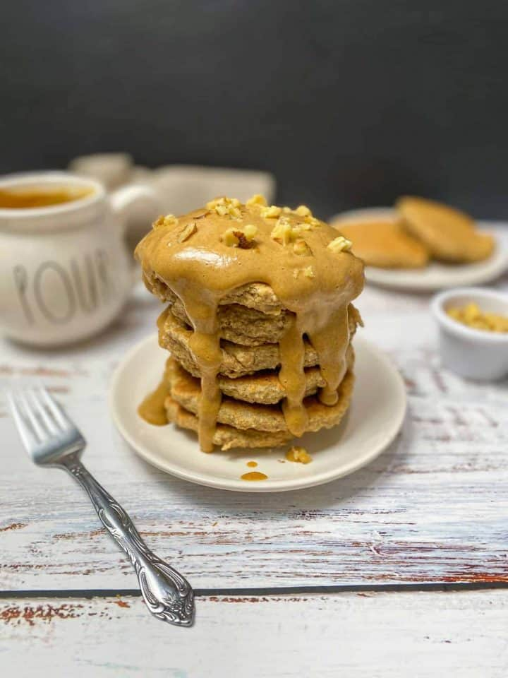 stack of pancakes with peanut butter caramel on top and dripping down the sides