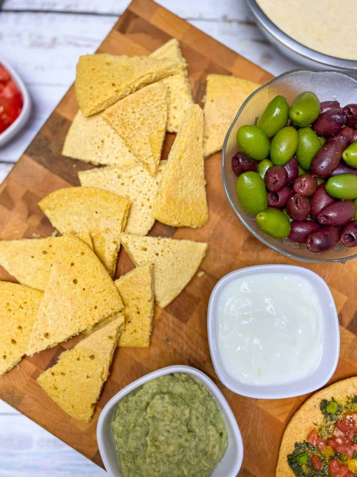 triangular wedges of socca on cutting board with bowl of olives and dips