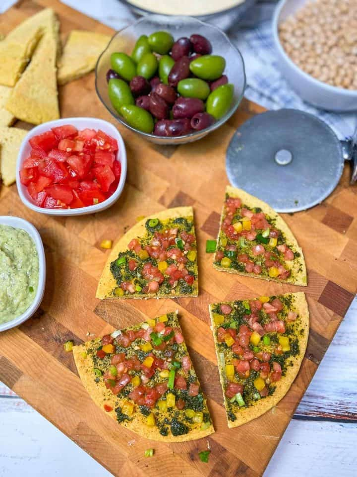 chickpea flatbread pizza cut into four slices on cutting board