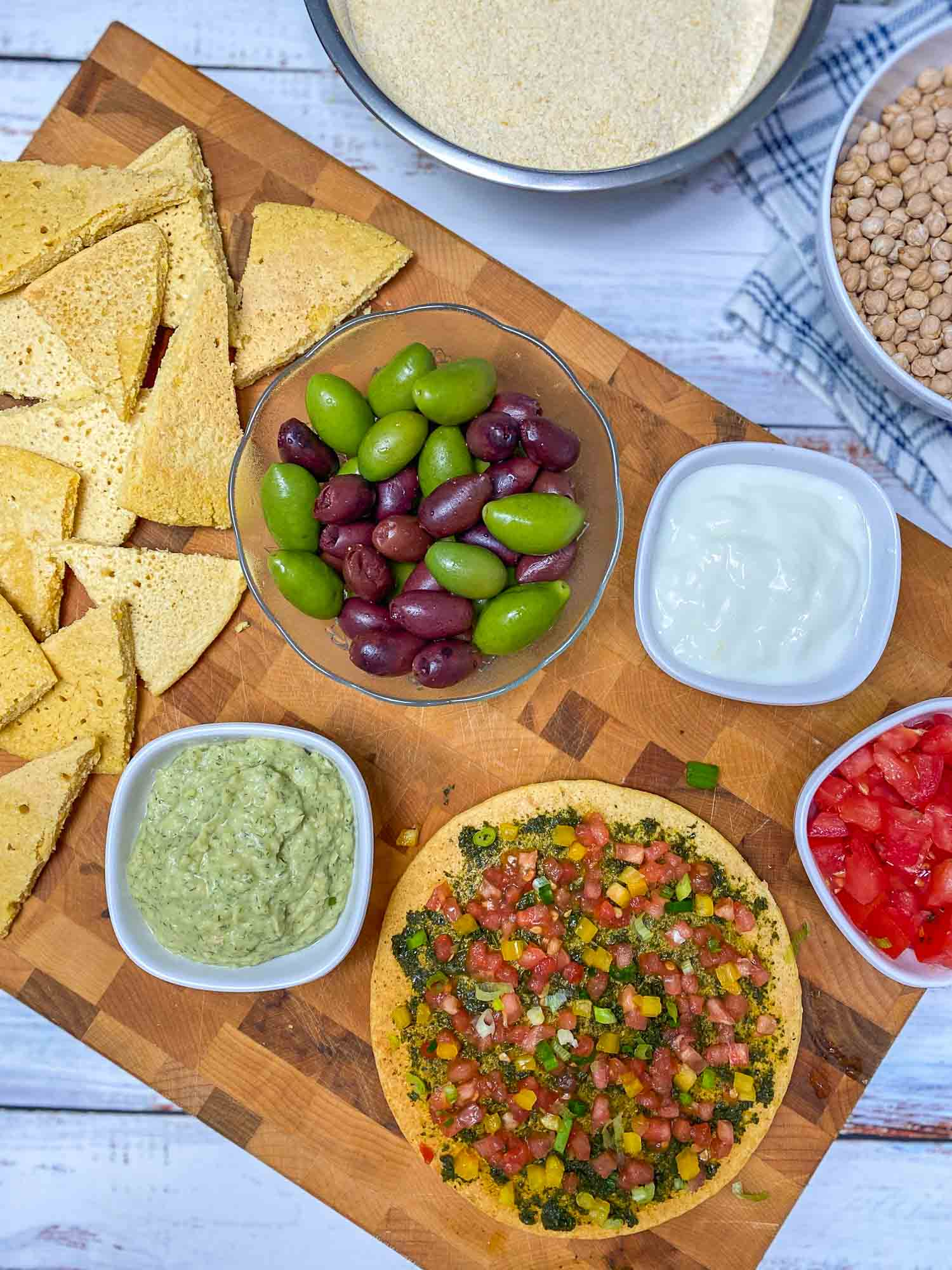 cutting board with pizza, pita wedges, dips and olives