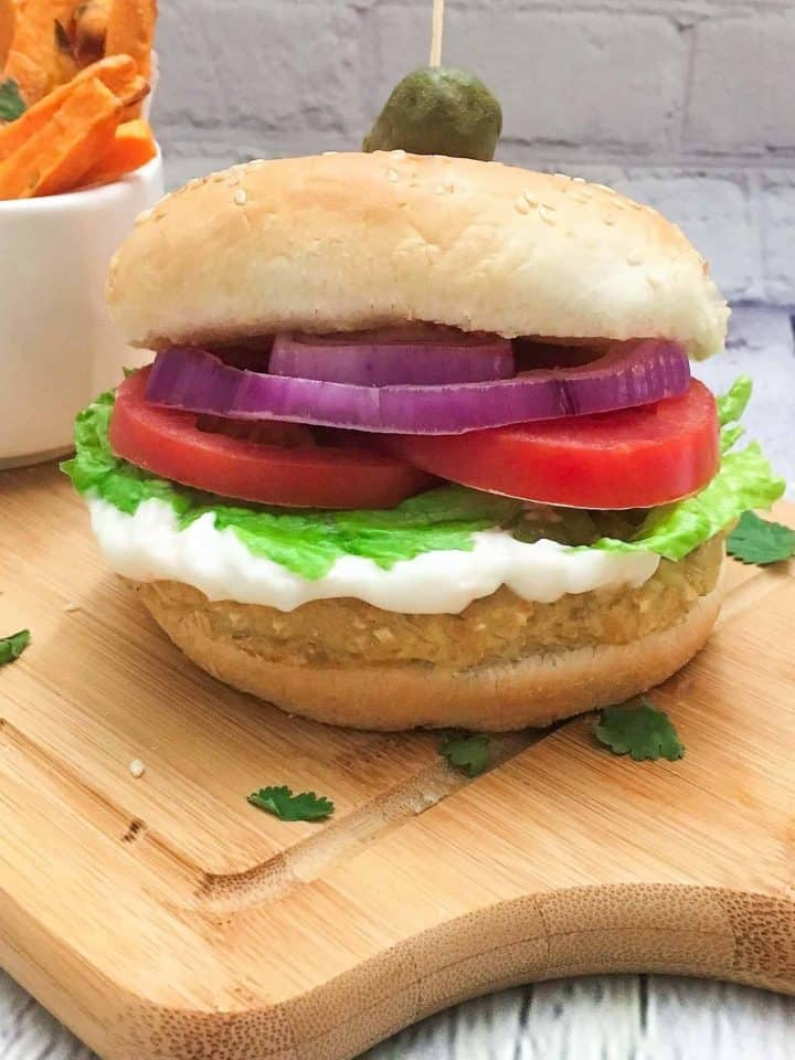 vegan chicken burger in bun with onion, tomato, lettuce and mayo