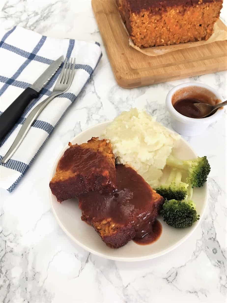chickpea meatloaf sliced on plate with smoked maple glaze on top