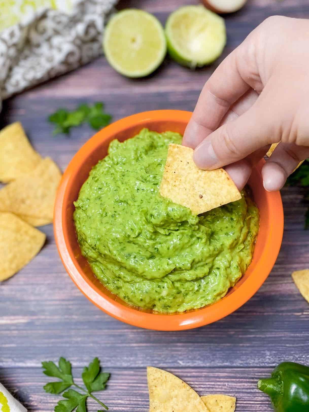 dipping tortilla chip into green dip