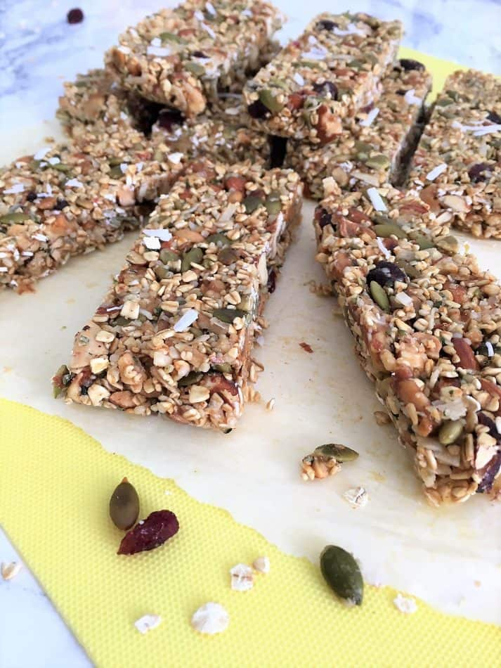 ten Homemade granola bars sitting on on yellow cutting board side view