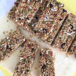 ten Homemade granola bars sitting on on yellow cutting board