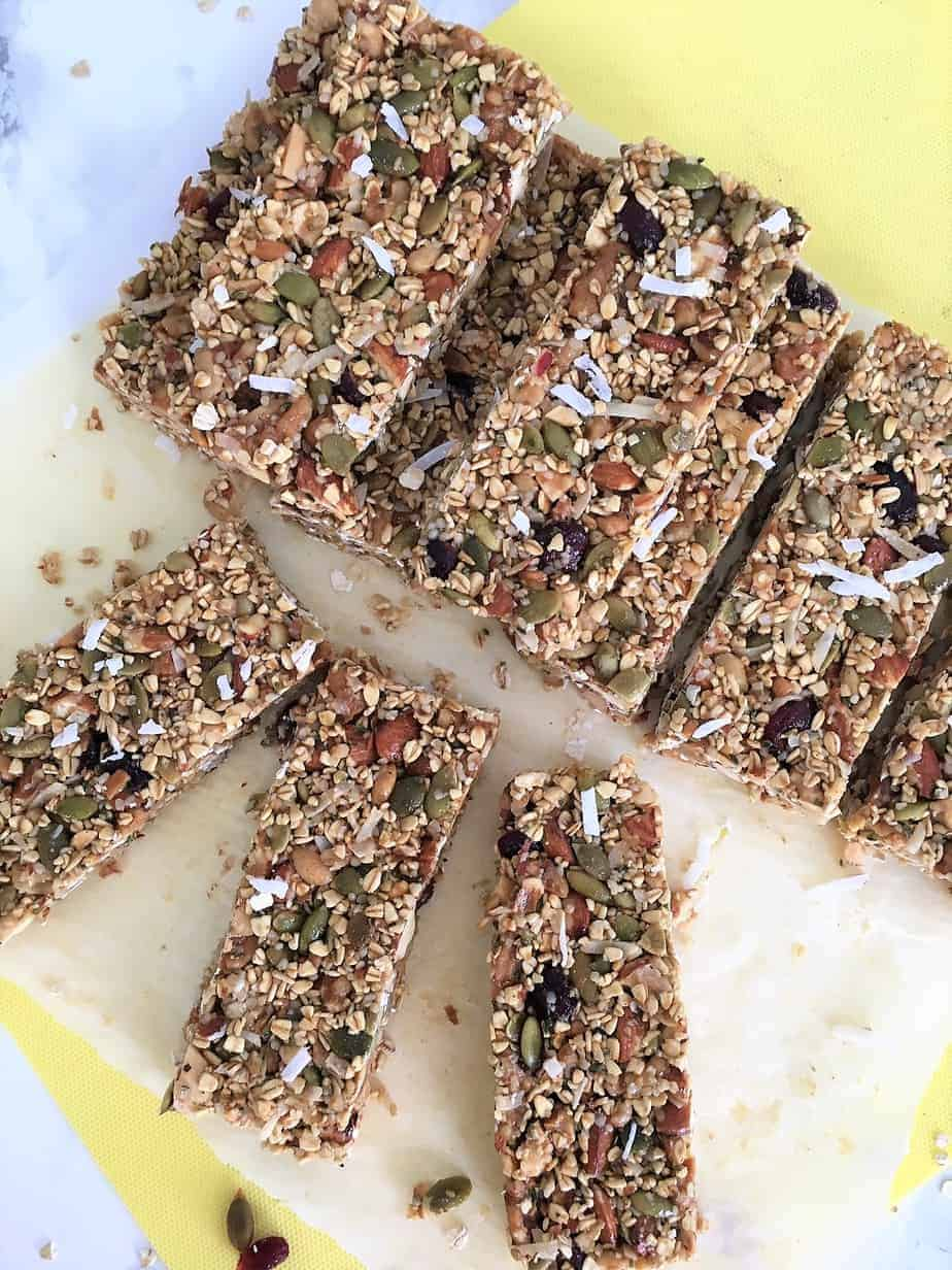 ten Homemade granola bars sitting on on yellow cutting board
