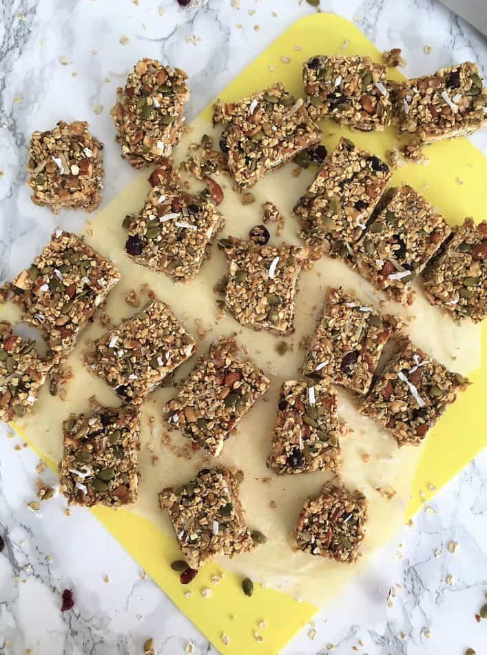 homemade granola bars cut into 20 squares sitting on yellow cutting board