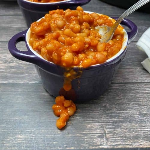 cooked beans in sauce spilling over the side of purple bowl